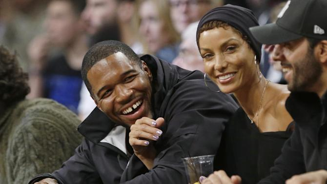 Michael Strahan, left, and Nicole Murphy smile during the first half of an NBA basketball game between the New York Knicks and the Brooklyn Nets on Tuesday, April 15, 2014, in New York