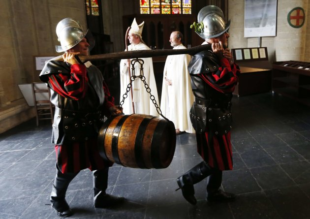 Members of the Knighthood of the Brewers' Mash staff carry a barrel of beer inside the Sint-Gudule Cathedral in Brussels