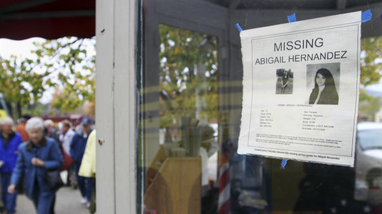 FILE - In this Oct. 16, 2013 file photo, tourists walk by an information booth in North Conway, N.H., bearing a poster of missing teenager Abigail Hernandez, 14, who disappeared on Oct. 9, 2013, after leaving school. New Hampshire Attorney General Joseph Foster said Monday, July 21, 2014, that Abigail Hernandez was reunited with her family Sunday evening. (AP Photo/Jim Cole, File)