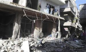 People gather around wreckage after a car bomb exploded in the Tadamon district of southern Damascus