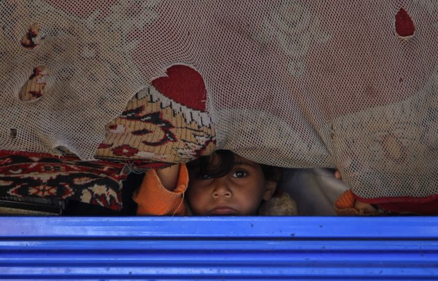 A girl looks out from a curtain at the back of a truck in Sanaa