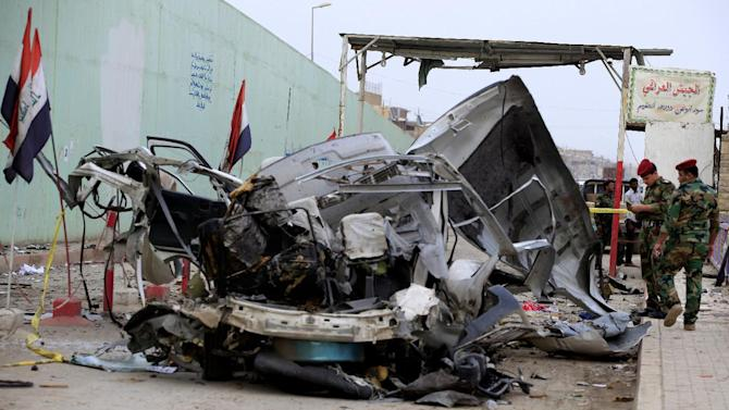 """Security forces personnel inspect the scene of a car bomb attack in the Husseiniyah suburb of northeastern Baghdad, Iraq, Monday, May 6, 2013. Two car bombs blew up in a Baghdad suburb, killing and wounding dozens of people, police said, in the deadlier of two attacks Monday that left at least 10 dead in the Iraqi capital. Arabic, top right, reads, """"the Iraqi military, is the wall of the nation, and the great shield."""" (AP Photo/ Karim Kadim)"""