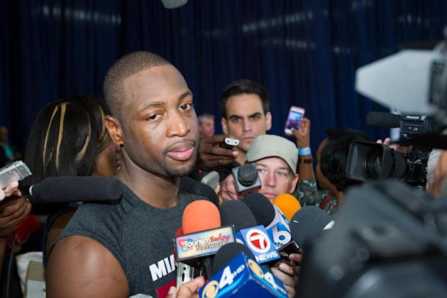 Miami Heat point guard Dwayne Wade speaks to reporters during a break from a training camp session at the Atlantis Resort in Paradise Island, Bahamas, Tuesday, Oct. 1, 2013. The two-time defending NBA