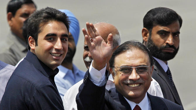 FILE - In this Sunday, April 8, 2012 file photo, Pakistan President Asif Ali Zardari, right, waves while arriving at the Palam Airfield with his son Bilawal Bhutto Zardari, left, in New Delhi, India. Members of Pakistan's outgoing ruling party say late Prime Minister Benazir Bhutto's son may play a less prominent role in the upcoming election campaign because of security concerns and political infighting. (AP Photo/Saurabh Das, File)