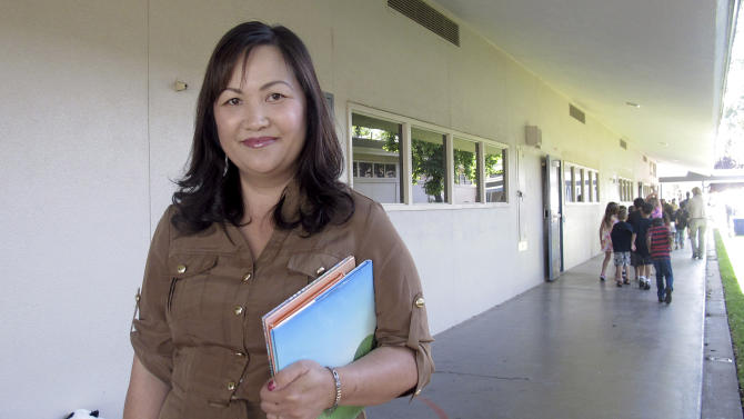 In this photo taken June 6, 2012, Misty Her, assistant superintendent with the Fresno Unified School District, talks to children about her job and encourages them to read at Cole Elementary School in Clovis, Calif. Hmong refugees migrated in large numbers to California's Central Valley after fighting in America's secret war in Laos. (AP/Gosia Wozniacka)