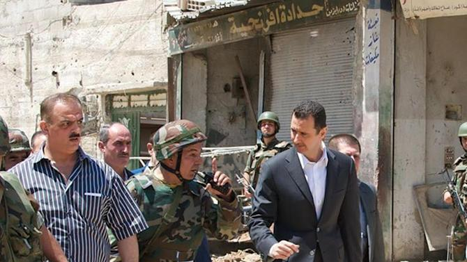 This image posted on the official Facebook page of the Syrian Presidency on Thursday, Aug. 1, 2013 purports to show Syrian President Bashar Assad walking with soldiers with during Syrian Arab Army day in Darya, Syria. Syrian state-run TV says Assad has visited a tense Damascus suburb to inspect his troops on the occasion of the country's Army Day. The visit on Thursday is Assad's first known public trip outside the capital, his seat of power, since he visited the Baba Amr district in the central city of Homs after troops seized it from rebels in March 2012. Daraya, just south of Damascus, was held by rebels for a long time and it took the army weeks of heavy fighting to regain control earlier this year. (AP Photo/Syrian Presidency via Facebook)