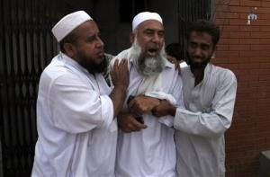 A man cries over the death of his brother, who was killed in a bomb blast, at a hospital in Peshawar