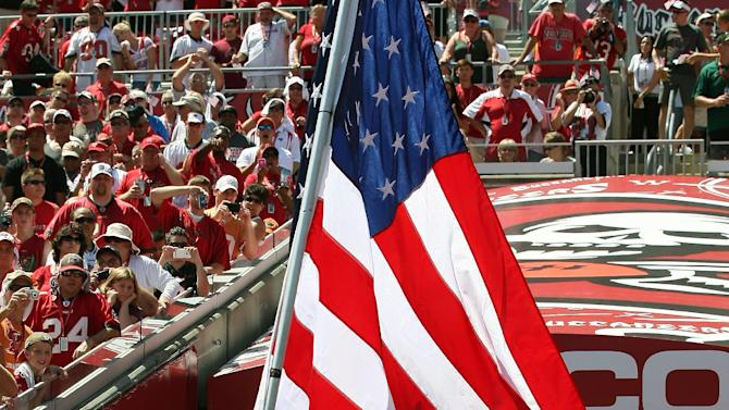 Tampa Bay Buccaneers tight end Kellen Winslow (82) carries a United States flag as he runs onto the field during player introductions before an NFL football game against the Detroit Lions, Sunday, Sept. 11, 2011, in Tampa, Fla. (AP Photo/Margaret Bowles)