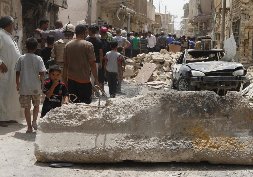 People inspect the scene of a car bomb attack in the Washash neighborhood of Baghdad, Iraq, Thursday, June 28, 2012. Police say a series of bombs around Iraq's capital have killed and wounded scores of people. (AP Photo/Karim Kadim)