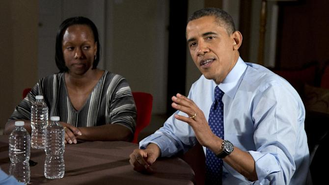High school English teacher Tiffany Santana listens at left as President Barack Obama speaks to the media during a visit with middle class taxpayers to discuss the importance of extending income tax cuts for Americans and small businesses, Thursday, Dec. 6, 2012, in Falls Church, Va.   (AP Photo/Carolyn Kaster)
