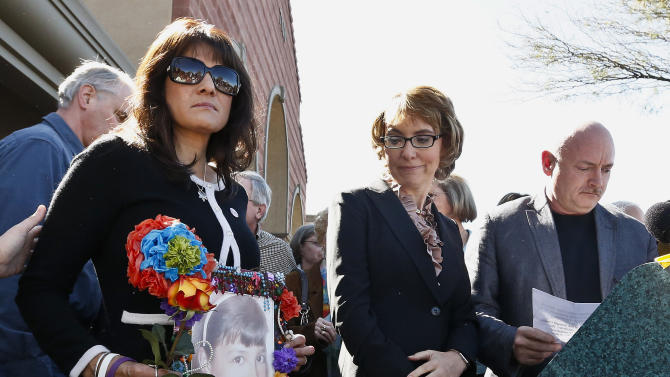 Former Rep. Gabrielle Giffords, center, looks at a photo of Christina-Taylor Green, as it is held by her mother Roxanna Green, left, as Giffords' husband Mark Kelly prepares to speak as they all returned to the site of a shooting that left her critically wounded, and many others killed, including the nine-year-old Green, to urge key senators to support expanded background checks for gun purchases, Wednesday, March 6, 2013, in Tucson, Ariz. (AP Photo/Ross D. Franklin)