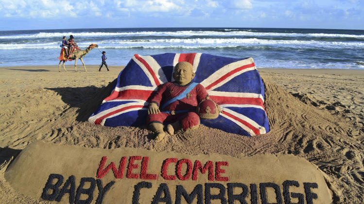 Tourists ride a camel past a sand sculpture created by sand artist Sudarshan Pattnaik to celebrate the birth of the Prince of Cambridge, the son of Britain's Prince William and Kate, Duchess of Cambridge, at a beach in Puri, India, Tuesday, July 23, 2013. (AP Photo)