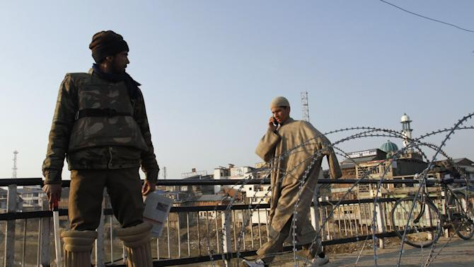 A Kashmiri civilian walks past an Indian policeman standing near a barbed wire during curfew in Srinagar, India, Saturday, Feb. 9, 2013. A Kashmiri man Mohammed Afzal Guru, convicted in the 2001 attack on India's Parliament, has been hanged in an Indian prison, a senior Indian Home Ministry official said Saturday. On Saturday morning thousands of police and paramilitary troops had fanned out across Indian Kashmir anticipating that protests and violence might follow news of the execution. (AP Photo/Mukhtar Khan)