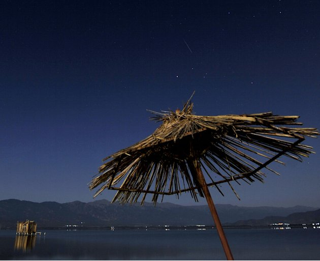 A meteor shines while entering the earth's atmosphere, center top, during the Perseid Meteor Shower observed early Saturday, Aug. 13, 2011, in this long exposure picture taken from Dojran Lake shore i