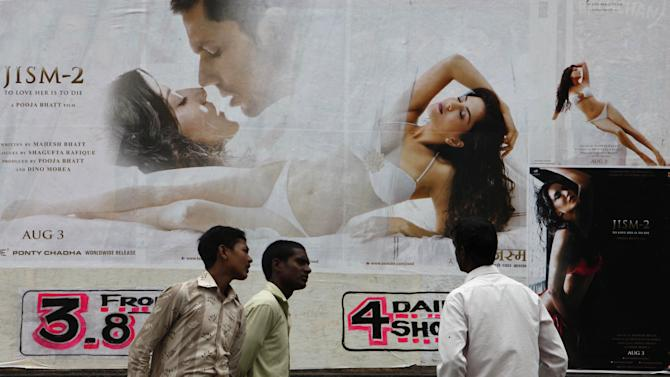 """An Indian man watches a poster of Bollywood film """"Jism 2""""  displayed outside a cinema in Hyderabad, India, Thursday, Aug. 2, 2012.  """"Jism 2"""" stars a hard-core porn actress, and it does have that pesky title. But it's not a porn movie. Bollywood is certainly not ready for that. The film, which will be released across India on Friday, is pushing the ever-widening sexual boundaries enjoyed by many in urban India.  (AP Photo/Mahesh Kumar A.)"""
