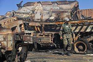 An Afghan policeman stands near a destroyed NATO supply…