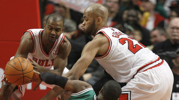Boston Celtics point guard Rajon Rondo (9) loses control of the ball as Chicago Bulls point guard John Lucas, left, and forward Taj Gibson, right, close in during the second half of an NBA basketball game on Thursday, Feb. 16, 2012, in Chicago. The Bulls won 89-80. (AP Photo/Charles Rex Arbogast)
