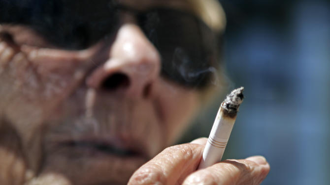FILE - In this June 11, 2007 file photo, Helen Heinlo smokes outside of a coffee shop in Belmont, Calif. Some smokers trying to get coverage in 2014 under President Barack Obama's health care law may get a break from tobacco-use penalties that could have made their premiums unaffordable. The Obama administration _ in yet another health care overhaul delay _ has quietly notified insurers that a computer system glitch will limit penalties that the law says the companies may charge smokers. A fix will take at least a year to put in place. (AP Photo/Paul Sakuma, File)