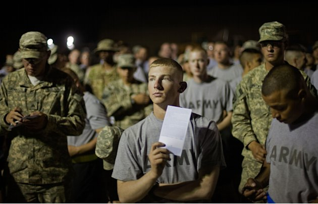 Pfc. Dillon Wall, 19, center, of Muldrow, Okla., with the U.S. Army's 4th Brigade Combat Team, 101st Airborne Division out of Fort Campbell, Ky., holds his U.S. Customs form while listening to instruc