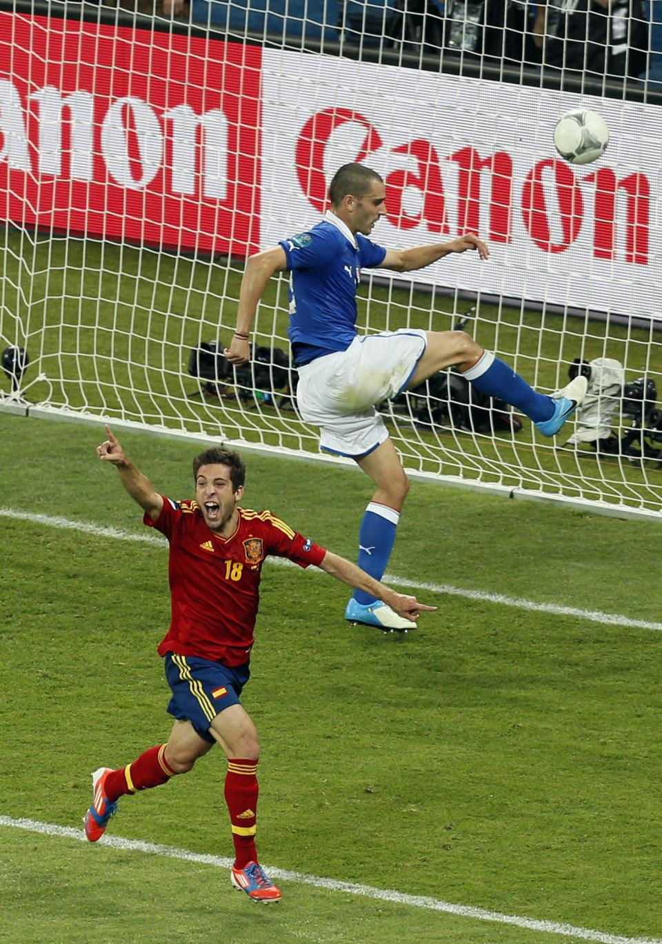 Spain's Jordi Alba celebrates scoring his side's second goal as Italy's Leonardo Bonucci kicks the ball in anger during the Euro 2012 soccer championship final  between Spain and Italy in Kiev, Ukraine, Sunday, July 1, 2012. (AP Photo/Vadim Ghirda)