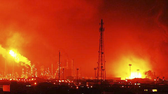 Fire rises over Amuay refinery near Punto Fijo, Venezuela, Saturday, Aug. 25, 2012. A huge explosion rocked Venezuela's biggest oil refinery, killing at least 19 people and injuring dozens, an official said. (AP Photo/Daniela Primera)