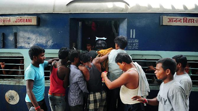Indian passengers board an overcrowded train at Allahabad Junction on June 30, 2014, Prime Minister Narendra Modi's new government is to roll out plans for a network overhaul