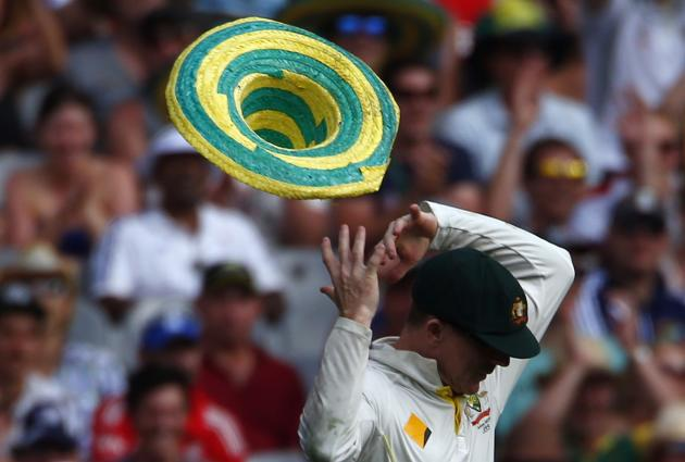A hat that blew onto the field, is blown off the head of Australia's Rogers after he put it on during the first day of the fourth Ashes cricket test against England, at the Melbourne cricket groun