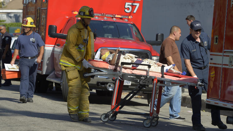A young victim is transported by Los Angeles city firefighters after a car driven by a 100-year-old went onto a sidewalk and plowed into a group of parents and children outside a South Los Angeles elementary school, Wednesday, Aug. 29, 2012, in Los Angeles. Nine children and two adults were injured in the wreck. (AP Photo/Mark J. Terrill)