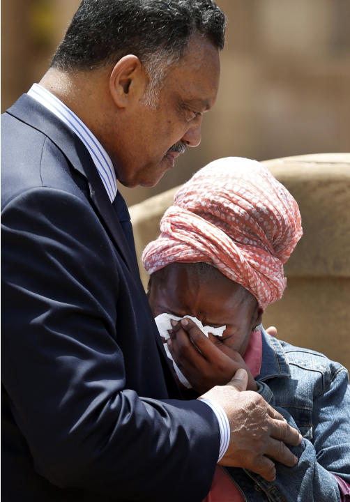 U.S. civil rights leader Jackson comforts a woman after she paid respects to former South African President Mandela in Pretoria