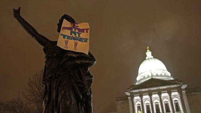 "FILE  - In this Feb. 21, 2011 file photo, a sign that says ""I support my teacher"" hangs on a statue outside the state Capitol in Madison, Wis. Twice as many public school teachers decided to retire this year as in each of the past two years, the leading edge of a mass exodus of public employees who decided to hang it up rather than pay more for their health insurance and pension benefits as required under changes pushed by Gov. Scott Walker and the Republican Legislature.  (AP Photo/Jeffrey Phelps, File)"