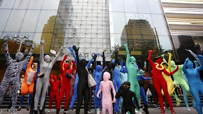 Participants wearing Zentai costumes pose for photos during a march down the shopping district of Orchard Road during Zentai Art Festival in Singapore
