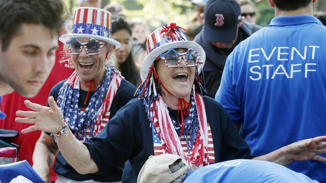 Gloria Kelley, center, of Gardner, Mass., laughs as she passes through security with Linda Stacy, of Ashby, Mass., behind left, before rehearsal for the annual Boston Pops orchestra Fourth of July concert on the Esplanade in Boston, Friday, July 3, 2015. (AP Photo/Michael Dwyer)