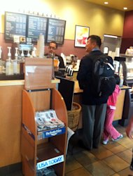 In this photo provided by ZhaoHui Tang, former Washington Gov. Gary Locke, who is the first Chinese-American ambassador to China, orders coffee at Seattle Tacoma International Airport on Aug. 12, 2011. ZhaoHui Tang, a businessman who snapped a photo of Locke carrying his own backpack and ordering his own coffee at Seattle-Tacoma International Airport says he's surprised by the big, admiring response the picture generated among Chinese citizens not used to such frugality. (AP Photo/ZhaoHui Tang )
