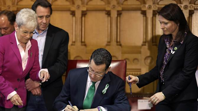 In this April 4, 2013, photo, Connecticut Gov. Dannel P. Malloy, center, signs legislation at the Capitol in Hartford, Conn., that includes new restrictions on weapons and large capacity ammunition magazines, a response to last year's deadly school shooting in Newtown. Neil Heslin, behind left, father of Sandy Hook shooting victim Jesse Lewis, Nicole Hockley, right, mother of Sandy Hook School shooting victim Dylan, and Conn. Lt. Gov. Nancy Wyman, left, watch. (AP Photo/Steven Senne)