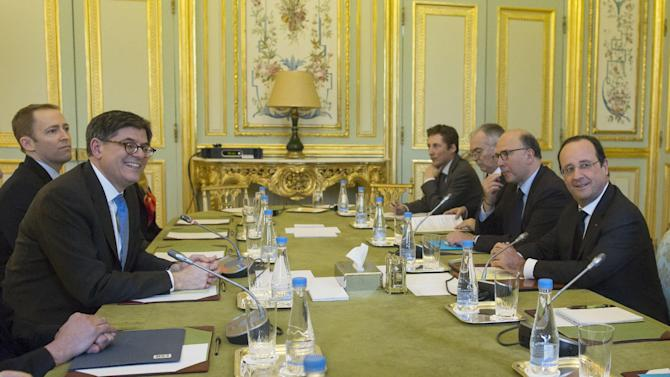 U.S. Treasury Secretary Jack Lew, left, French President Francois Hollande, right, and France's Finance Minister Pierre Moscovici, 2nd right, pose prior to a meeting at the Elysee Palace in Paris, Tuesday, Jan. 7, 2014. Lew is on a European tour for two days. (AP Photo/Ian Langsdon, Pool)