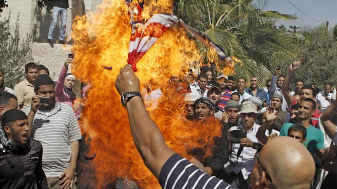 An Islamist Jordanian protester burn the U.S. flag near the U.S. embassy in Amman, Jordan, Friday, Sept. 14, 2012, as part of widespread anger across the Muslim world about a film ridiculing Islam's Prophet Muhammad.(AP Photo/Raad Adayleh)