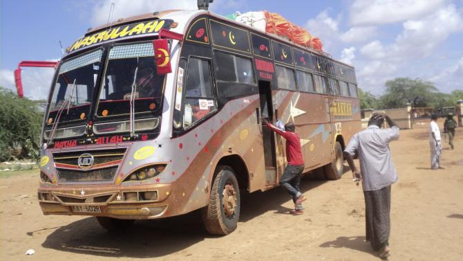 Rescue workers walk near a Nairobi-bound bus that was ambushed outside Mandera town