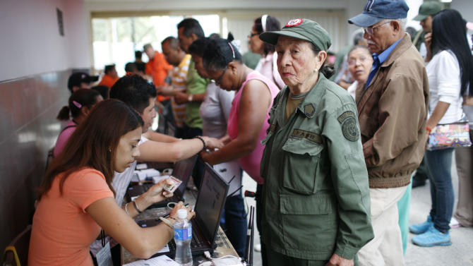 An elderly woman wearing a Bolivarian militia uniform stands before an election worker, who holds her identification as part of the voting process, before casting her ballot in the presidential election at a polling station in the Petare neighborhood of Caracas, Venezuela, Sunday, Oct. 7, 2012.  President Hugo Chavez is running against opposition candidate Henrique Capriles. The Bolivarian militia, created by Chavez, is estimated to number more than 100,000 who do not report to the armed forces. (AP Photo/Ariana Cubillos)
