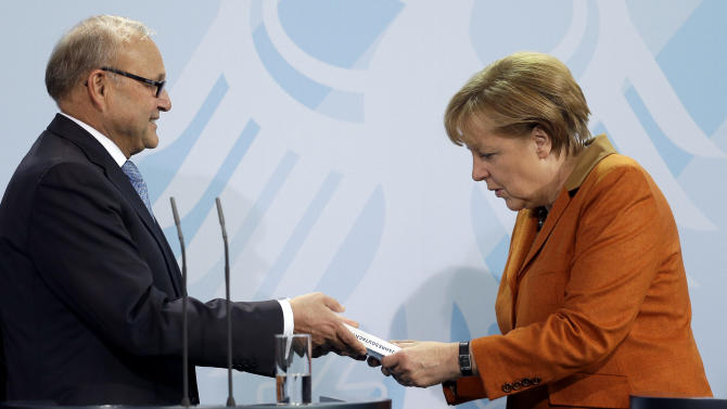 Economy specialist Wolfgang Franz, left, hands over the prognosis for Germany's economy in the upcoming year to German Chancellor Angela Merkel at the chancellery in Berlin, Germany, Wednesday, Nov. 7, 2012. (AP Photo/Michael Sohn)