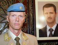 UN top observer Major General Robert Mood stands next to a portrait of Syrian President Bashar al-Assad upon his arrival in Damascus in April. Mood said on Wednesday he was &quot;deeply disturbed&quot; by a newly discovered massacre in Syria, as the opposition insisted Assad must step down if a peace plan is to be saved