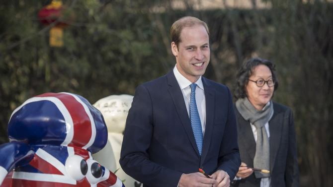 "Britain's Prince William, Duke of Cambridge, poses after painting the eye of a ""Shaun the Sheep"" sculpture at the British Ambassador's official residence in Beijing"