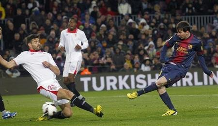 Barcelona's Lionel Messi scores a goal against Sevilla's Alberto Botia during their Spanish First division soccer league match at Camp Nou stadium in Barcelona
