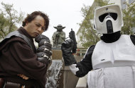 In this Aug. 2, 2011 photo, Matt Tolosa, left, who is dressed like the Star Wars movie character Anakin Skywalker, while his brother Dale Tolosa, right, who is dressed as a Stormtrooper, poses in front of a a life-sized replica of Yoda, George Lucas' master of the Force, at Lucasfilm Ltd. production studios in San Francisco. The production studio is one of many special sites visited by fans like the Tolosa brothers. (AP Photo/Paul Sakuma)