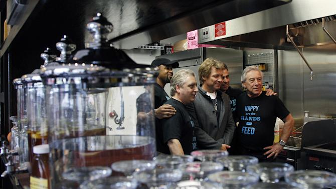 Rock star Jon Bon Jovi, center, poses with kitchen workers at the Soul Kitchen restaurant in Red Bank, N.J., Wednesday, Oct. 19, 2011, during the opening of the restaurant which is designed to help the hungry without the stigma of a soup kitchen. Diners pay whatever they're able to. (AP Photo/Mel Evans)