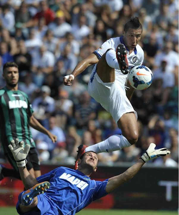Inter Milan's Saphir Taider of Algeria, top, scores past Sassuolo's goalkeeper Alberto Pomini, during their Serie A soccer match at Reggio Emilia's Mapei stadium, Italy, Sunday, Sept. 22, 2013