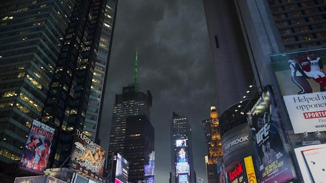 Storm clouds loom over Times Square as Manhattan braced for heavy weather, Thursday, July 26, 2012, in New York. The storm resulted in more than 20,000 customers without power in the Elmira area in upstate New York, where buildings were damaged, power lines and trees toppled, and hospitals placed on disaster status after a possible tornado hit the city Thursday afternoon. (AP Photo/John Minchillo)