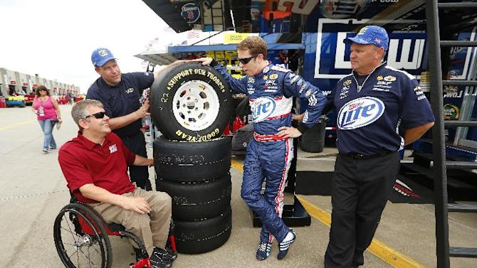 "IMAGE DISTRIBUTED FOR GOODYEAR- Brad Keselowski, right center, driver of the #2 Miller Lite Ford talks with Mike Savicki, left, Paralyzed Veterans of America member as Jim Davis, right, tire specialist for the #2 Miller Lite Ford and James Heath, left center, with Goodyear Racing and a retired Marine look on after Savicki helped deliver a new set of Goodyear tires featuring ""Support Our Troops"" on the sidewall at the Charlotte Motor Speedway as Goodyear kicks off the 4th Annual ""Goodyear Gives Back"" Program, on Thursday, May 23, 2013 in Concord, N.C. (Photo by Chris Keane/Invision for Goodyear/AP Images)"