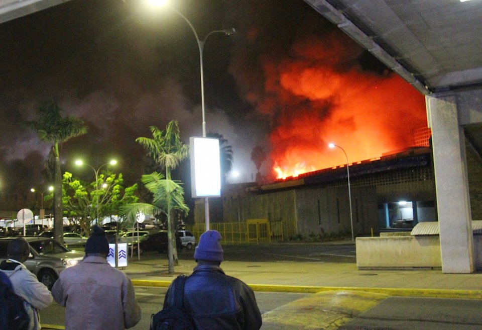 People watch a large blaze raging at the Jomo Kenyatta International Airport in Nairobi, Kenya, early Wednesday, Aug. 7, 2013. The Kenya Airports Authority said Wednesday that Kenya's main international airport has been closed until further notice so that emergency teams can battle the fire. (AP Photo/Kyodo News) JAPAN OUT, MANDATORY CREDIT
