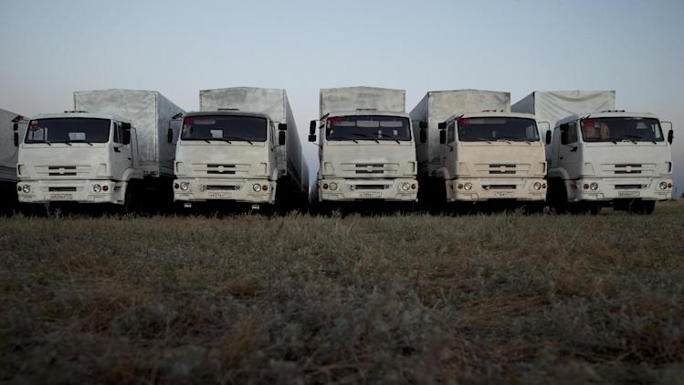 About 60 trucks forming part of a Russian aid convoy are parked in a field about 7 kilometers (4 miles) from a border control point with Ukraine in the Russian town of Donetsk, Rostov-on-Don region, Russia, Thursday evening, Aug. 21, 2014. (AP Photo/Pavel Golovkin)