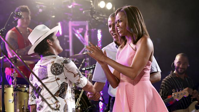 U.S. President Barack Obama and first lady Michelle Obama greet performer Bruno Mars during an Independence Day celebration on the South Lawn of the White House in Washington